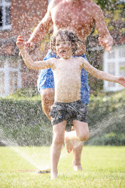 Father And Son Running Through Garden Sprinkler Stock photo © monkey_business