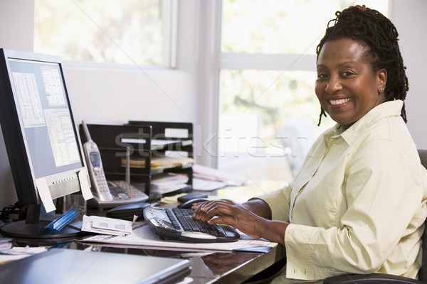 Woman in home office using computer and smiling Stock photo © monkey_business