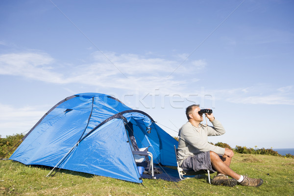 Man camping outdoors and looking through binoculars Stock photo © monkey_business