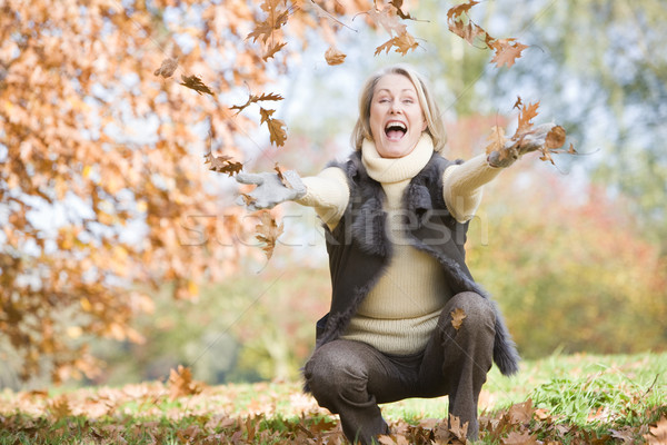 Senior woman throwing leaves in the air Stock photo © monkey_business