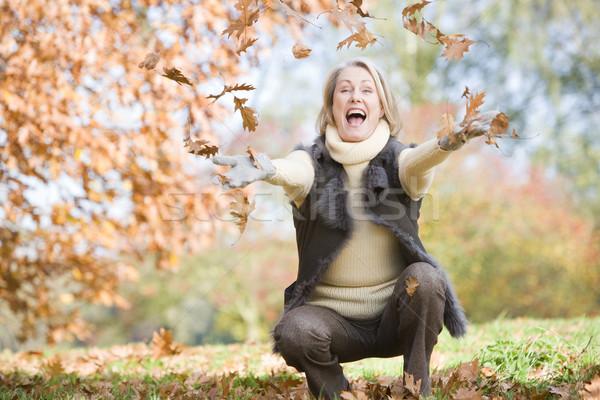 Idős nő dob levelek levegő őszi levelek Stock fotó © monkey_business