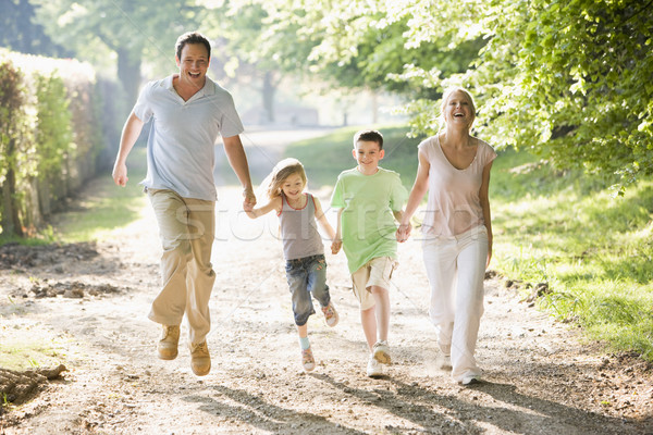 Family running outdoors holding hands and smiling Stock photo © monkey_business