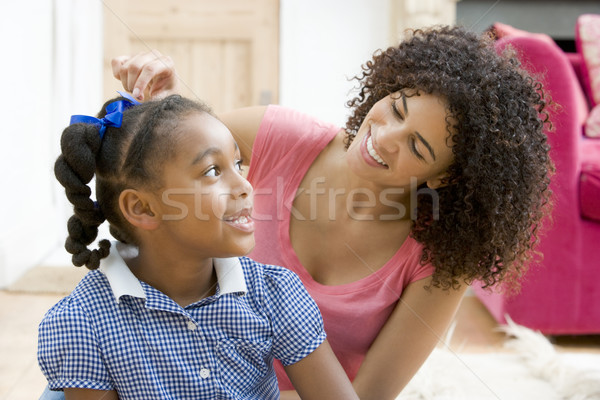 Woman in front hallway fixing young girl's hair and smiling Stock photo © monkey_business