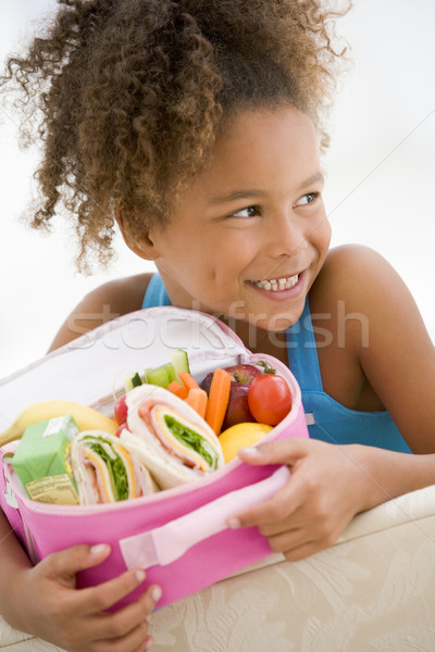 Young girl holding packed lunch in living room smiling Stock photo © monkey_business
