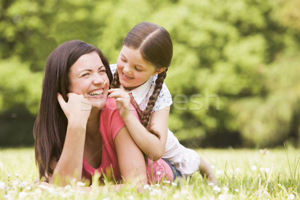 Mother and daughter lying outdoors with flower smiling Stock photo © monkey_business