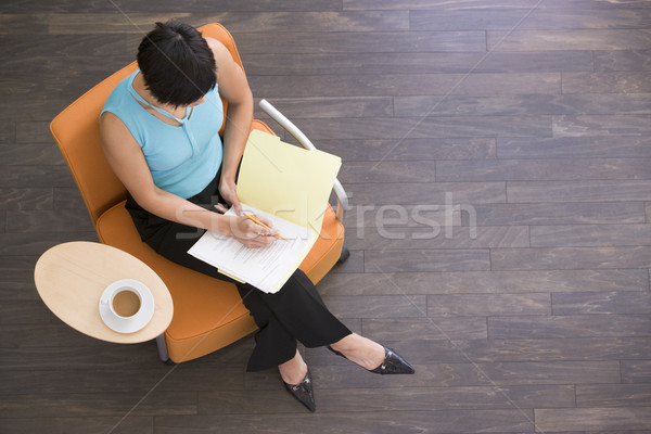 Businesswoman sitting indoors with coffee and folder Stock photo © monkey_business
