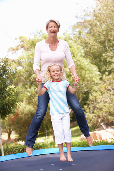 Mother And Daughter Jumping On Trampoline In Garden Stock photo © monkey_business