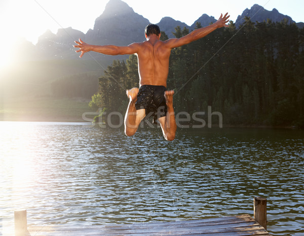 Young man jumping into lake Stock photo © monkey_business