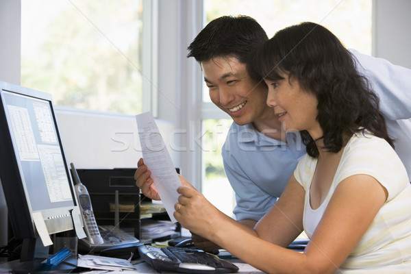 Couple in home office with computer and paperwork smiling Stock photo © monkey_business