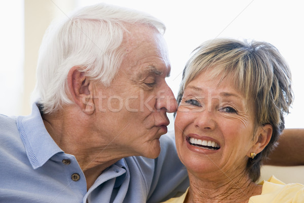 Stock photo: Couple relaxing in living room kissing and smiling