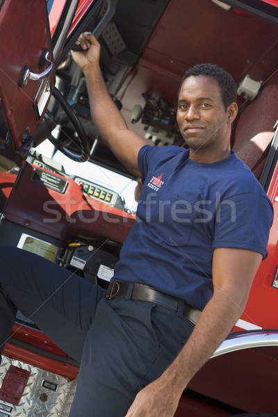 A firefighter standing by the cab of a fire engine Stock photo © monkey_business