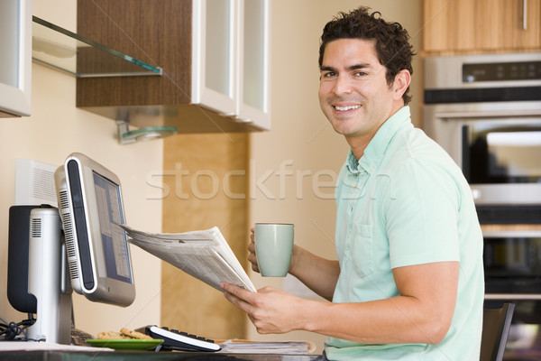 Man in kitchen with computer holding newspaper and coffee smilin Stock photo © monkey_business