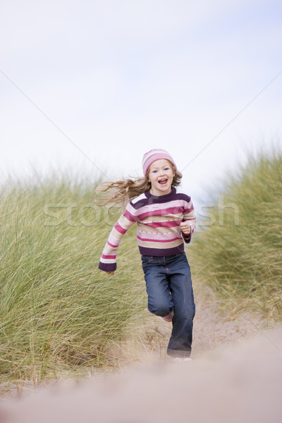 Stock photo: Young girl running on beach smiling