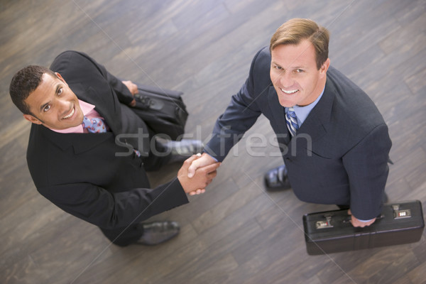 Two businessmen indoors shaking hands smiling Stock photo © monkey_business