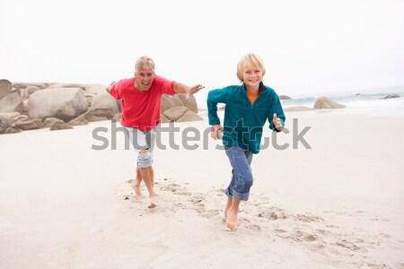 Grandfather Chasing Grandson Along Winter Beach Stock photo © monkey_business