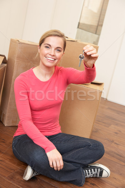 Young woman sits on the floor around boxes holding a key in her  Stock photo © monkey_business