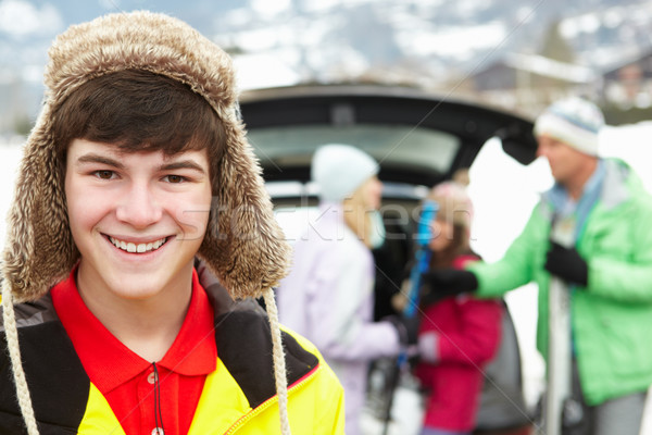 Teenage Boy Smiling At Camera Whilst Family Load Skis In Boot Of Stock photo © monkey_business