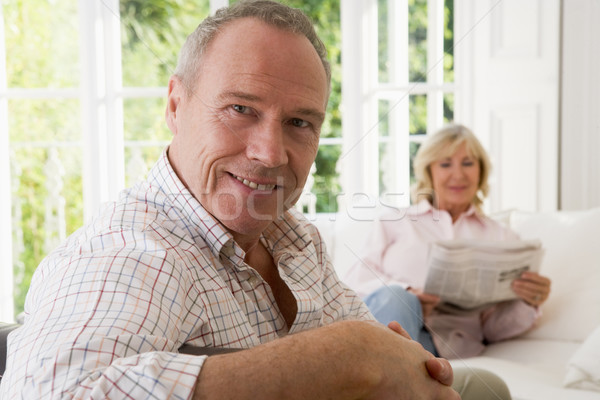 Man in living room smiling with woman in background reading news Stock photo © monkey_business