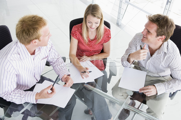 Three businesspeople in a boardroom looking at paperwork Stock photo © monkey_business