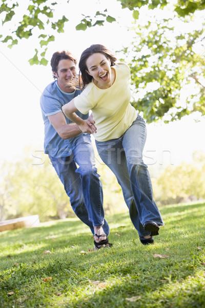 ストックフォト: カップル · を実行して · 屋外 · 手をつない · 笑みを浮かべて · 草