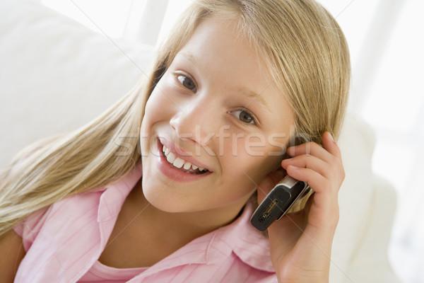 Giovane ragazza seduta divano parlando telefono cellulare ragazza Foto d'archivio © monkey_business