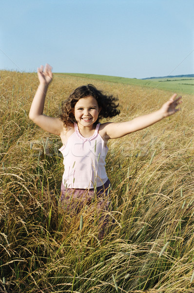 Stock photo: Young girl running outdoors smiling
