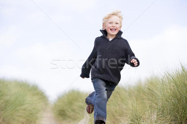 Młody chłopak uruchomiony plaży uśmiechnięty dziecko zimą Zdjęcia stock © monkey_business