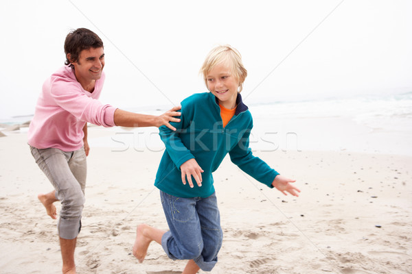 Father Chasing Son Along Winter Beach Stock photo © monkey_business