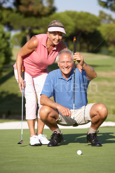 Senior Couple Golfing On Golf Course Lining Up Putt On Green Stock photo © monkey_business