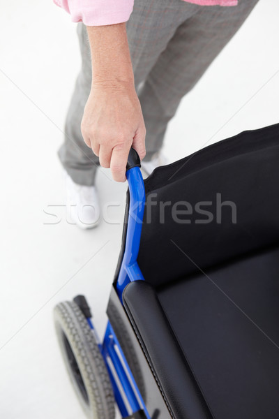 Woman pushing empty wheelchair Stock photo © monkey_business