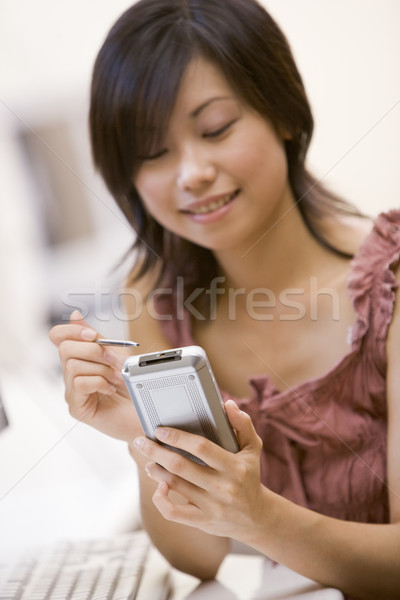Woman in computer room using personal digital assistant smiling Stock photo © monkey_business