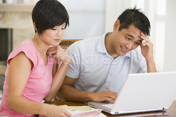 Couple in dining room with laptop looking unhappy Stock photo © monkey_business