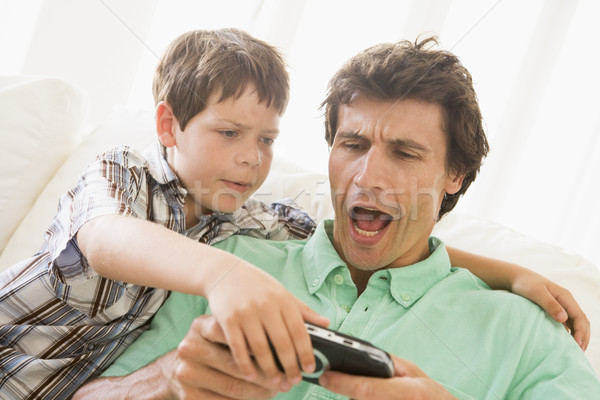 Young boy taking handheld game from unhappy man Stock photo © monkey_business