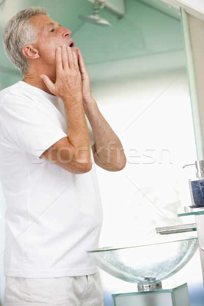 Man in bathroom applying aftershave and smiling Stock photo © monkey_business