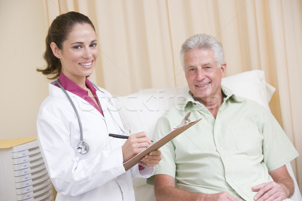 Doctor writing on clipboard while giving checkup to man in exam  Stock photo © monkey_business