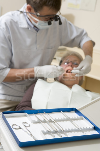 Dentist in exam room with woman in chair Stock photo © monkey_business