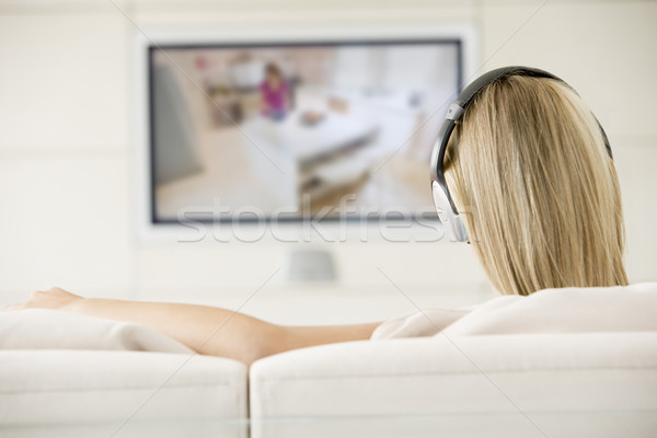Stock photo: Woman in living room watching television and wearing headphones