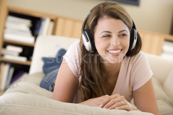 Woman in living room listening to headphones smiling Stock photo © monkey_business