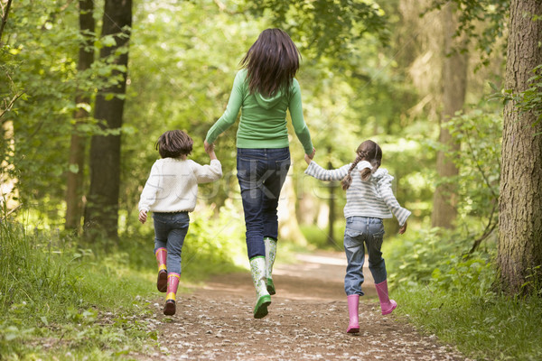 Mother and daughters skipping on path smiling Stock photo © monkey_business