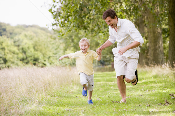 Foto stock: Filho · pai · corrida · caminho · de · mãos · dadas · sorridente · crianças