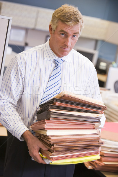 Businessman standing in cubicle with stacks of files Stock photo © monkey_business