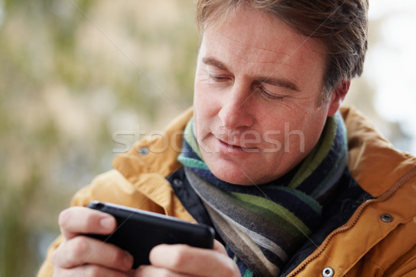 Man Texting On Smartphone Wearing Winter Clothes Stock photo © monkey_business