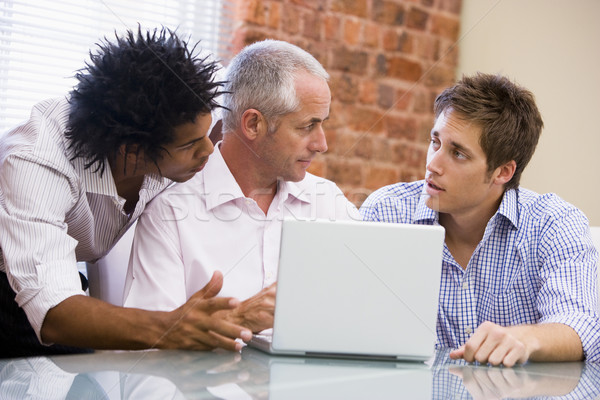 Three businessmen in office with laptop talking Stock photo © monkey_business
