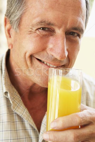 ストックフォト: シニア · 男 · 笑みを浮かべて · カメラ · 飲料 · オレンジジュース
