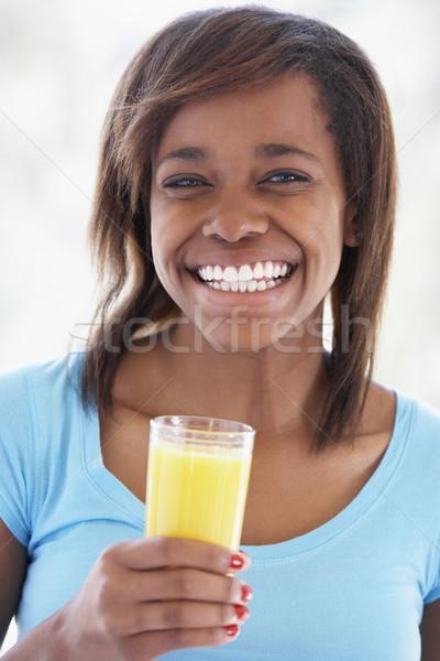 Adolescente potable fraîches jus d'orange fille maison Photo stock © monkey_business