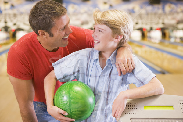 Stock photo: Man and young boy in bowling alley holding ball and smiling