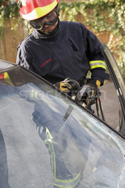 Firefighters breaking a car windscreen to help a car crash victi Stock photo © monkey_business