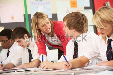 Teacher helping schoolchildren learn to tell time in primary cla Stock photo © monkey_business