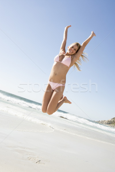 Young woman leaping on beach Stock photo © monkey_business