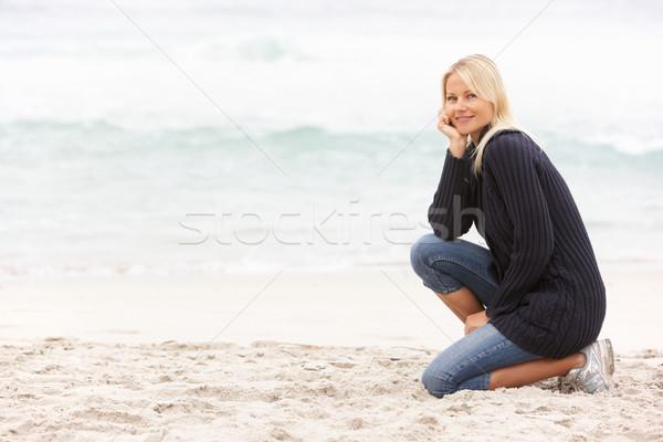 Fiatal nő ünnep térdel tél tengerpart nő Stock fotó © monkey_business